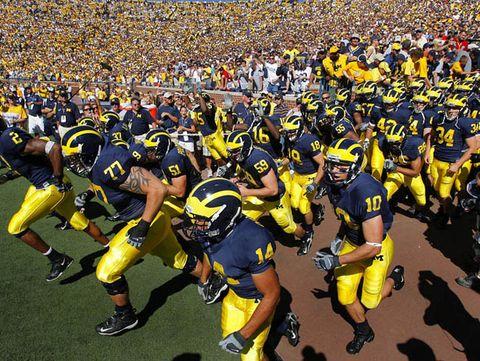 Yellow, Sports gear, Jersey, Human leg, Sport venue, Crowd, Football equipment, Competition event, Football gear, Team,