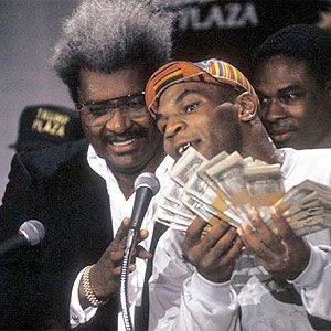 young mike tyson holding money at press conference with don king