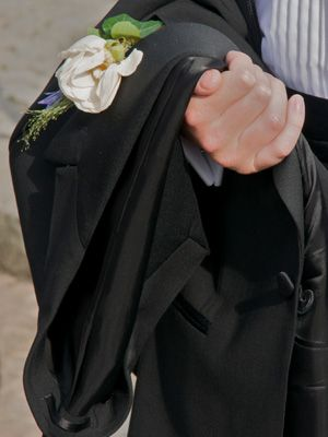groomsman holding coat jacket