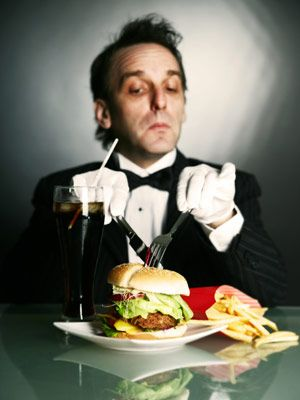 snooty restaurant critic eats a burger with a fork and knife