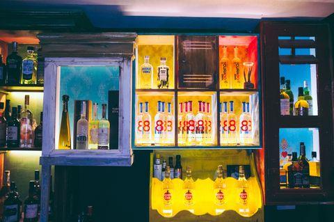 Yellow, Bottle, Drink, Alcohol, Majorelle blue, Liquid, Glass bottle, Alcoholic beverage, Shelving, Distilled beverage,