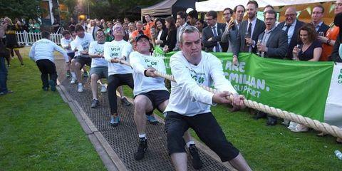 Leg, Human leg, Tug of war, Community, Athletic shoe, Crowd, Knee, Thigh, Active shorts, Crocodile,