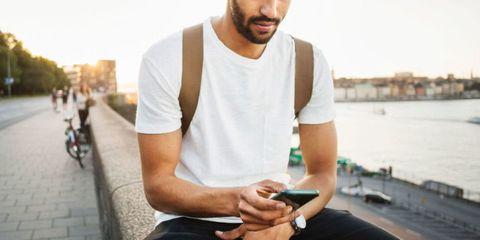 Gadget, Facial hair, T-shirt, Technology, Arm, Electronic device, Beard, Smartphone, Neck, Mobile phone,