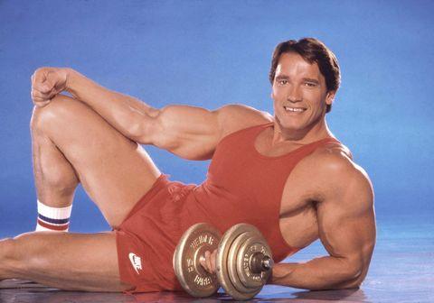arnold schwarzenegger relaxing with a weight