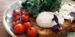 Close-Up Of Healthy Poached Eggs On Tasted Bread With Herbs And Cherry Tomatoes In Plate
