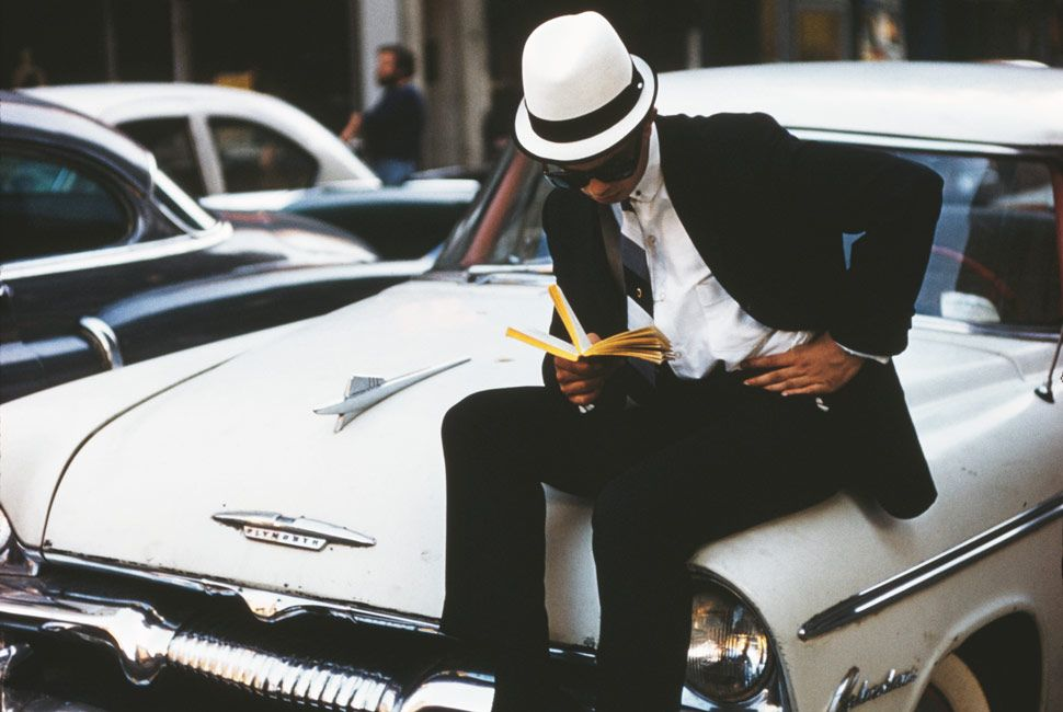 A sharply-dressed young man sitting on a Plymouth car and reading a book, New York City, June 1962. (Photo by Ernst Haas/Hulton Archive/Getty Images)