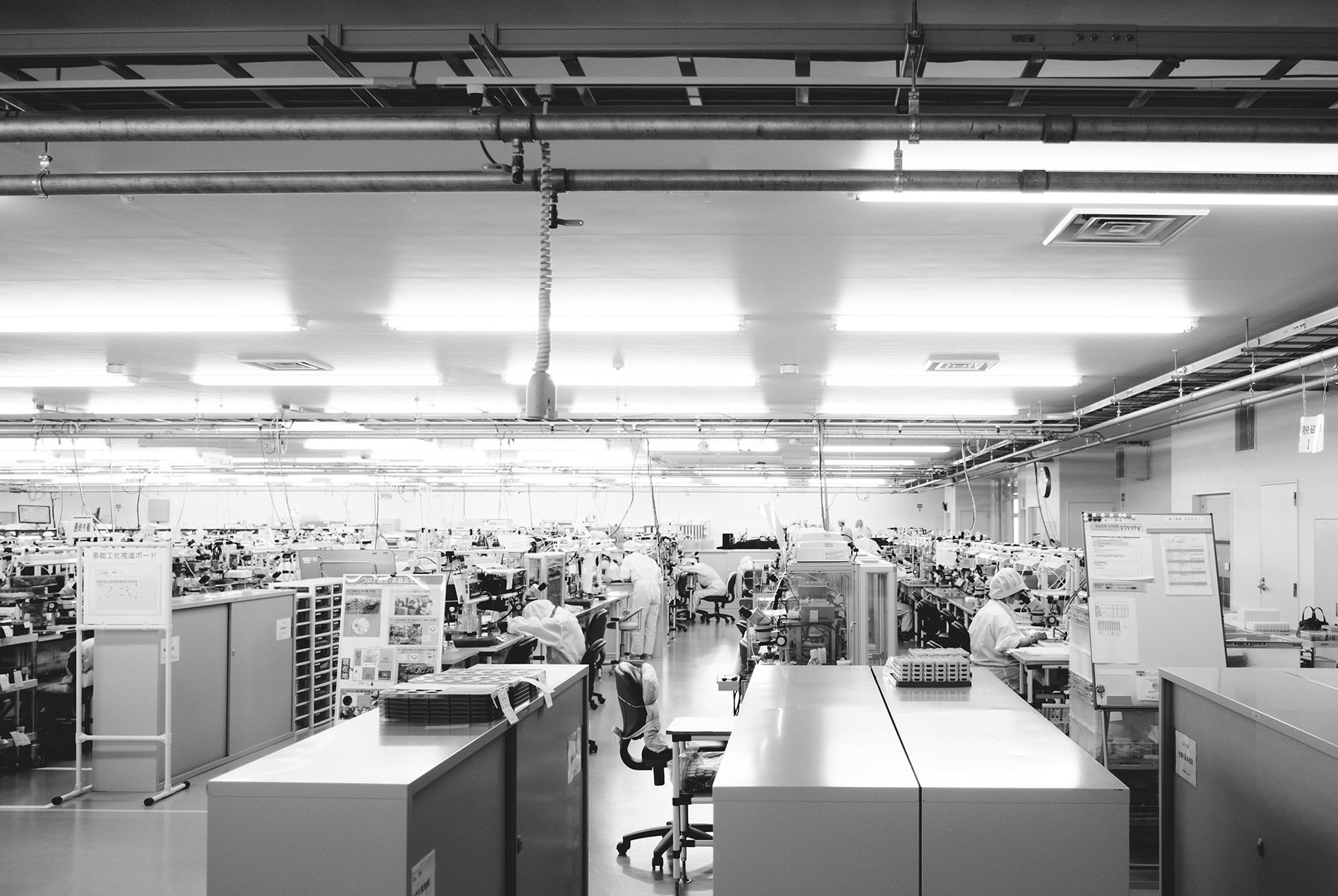 Citizen's watches are made using both human and robotic assembly. The factory is hushed and laboratory-like. Workers assemble in sync with robotic equipment.
