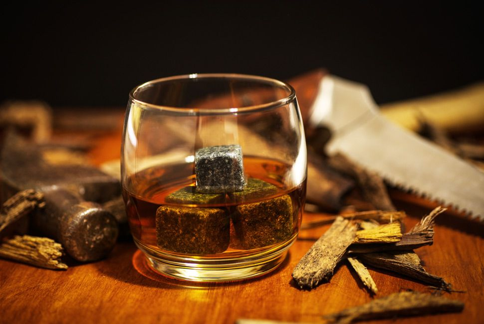 A glass of whiskey on the rocks in simple glass ware with whiskey stones in a carpentry work space with a hammer and saw with wood chips on top a wood desk.