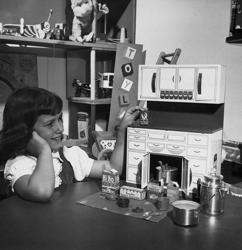 In the Darling Toy Store, a girl inspects a miniature kitchen cabinet stocked with pots, pans, and play food packages, New York, 1950. (Photo by PhotoQuest/Getty Images)