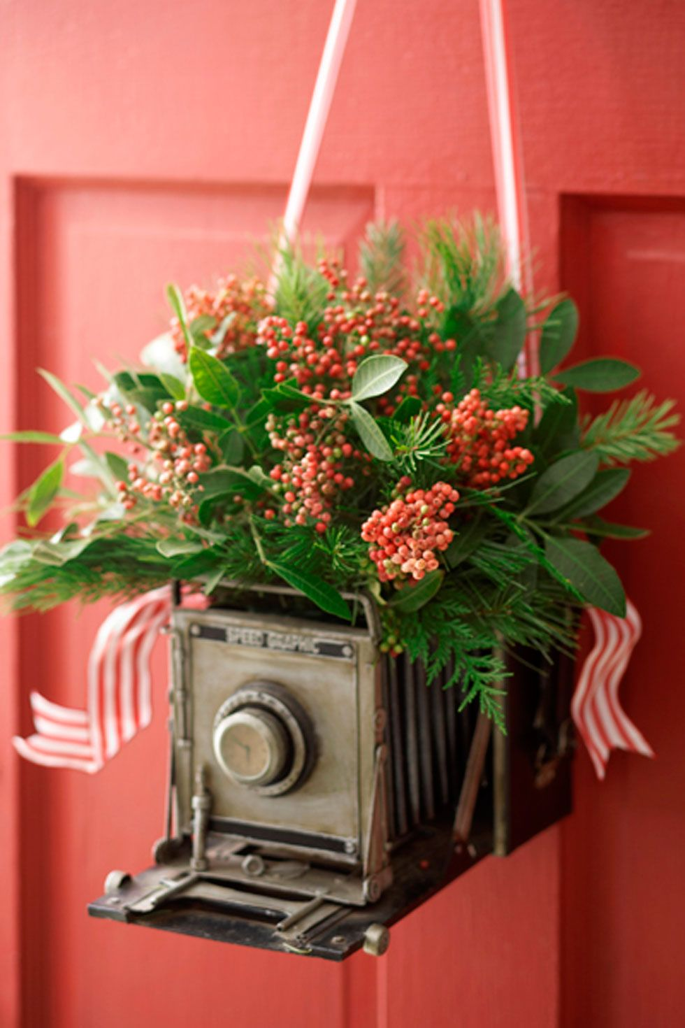 "Want to show off your love of antiques? Hang a vintage camera from your front door and fill with flowers and other greenery. Add small cuts of ribbon for extra charm.  <em>See more at <a target=""_blank"" href=""http://www.1800flowers.com/blog/julie/how-tos/give-a-personalized-wreath/?flws_rd=1"">Petal Talk</a>.</em>"