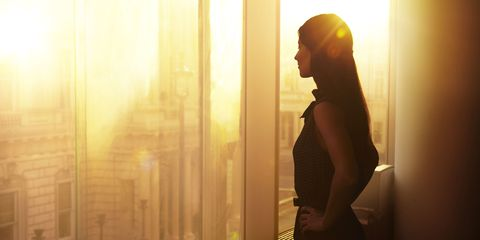 businesswoman looking out office window at sunrise