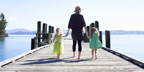 mom hold hands with two small daughters on a pier