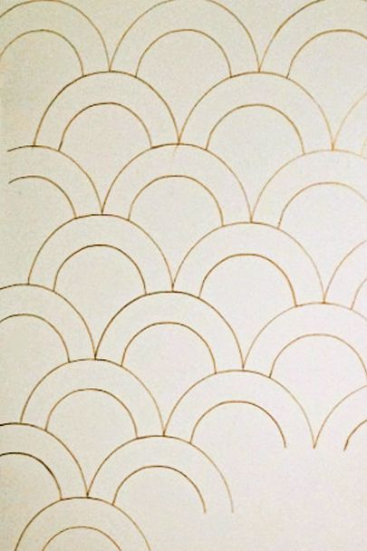 First, outline the arch of the larger scallop repeatedly on your wall using the metallic pen, connecting the arches on the sides. Create a second row beneath the first, staggering them so they fall between the arches of the previous row. Continue until your wall is covered, then go back and trace the entire form of the smaller scallop within each of the larger scallops.