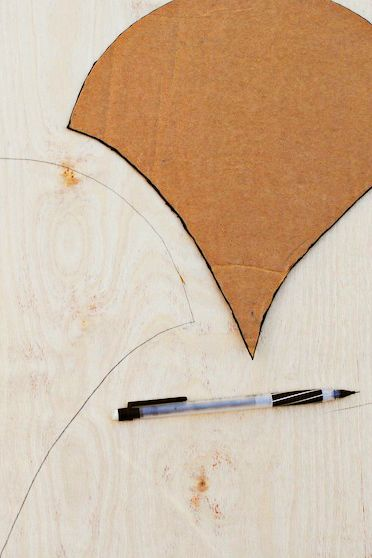 """Using thick cardboard, cut out two scallops (you can download the <a target=""""_blank"""" href=""""http://www.goodhousekeeping.com/home/craft-ideas/a32515/scallop-stencil-pdf/"""">template here</a>). Trace the outline of the smaller scallop onto a piece of 1/8"""" plywood. With industrial scissors or a jigsaw, cut around the edges. Repeat until you have enough scallops to cover your wall."""