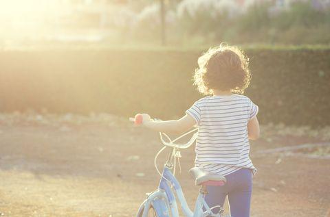 girl walking alone with her bike