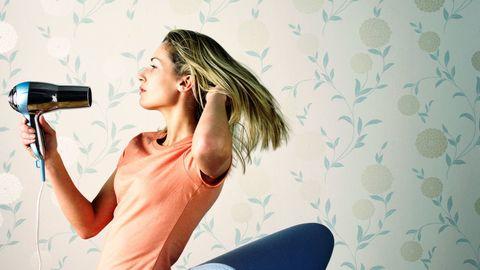 girl blow drying hair - bad things for hair