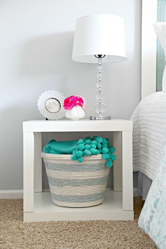 """A black plastic basket wouldn't normally fit so well in a serene bedroom. But wrapped in rope, it transforms into chic storage.  <a target=""""_blank"""" href=""""http://iheartorganizing.blogspot.com/2012/06/diy-rope-basket.html""""><em>Get the tutorial at I Heart Organizing »</em></a>"""