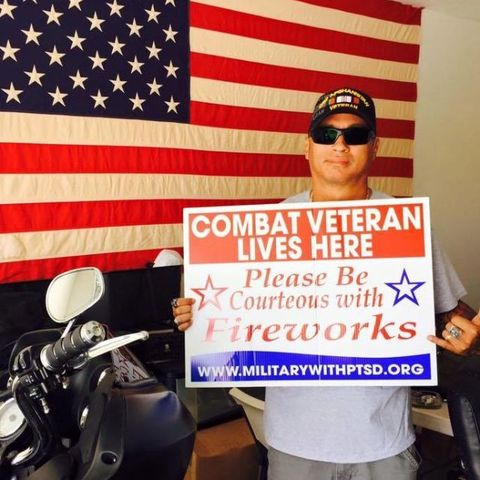 military veteran with flag and ptsd sign