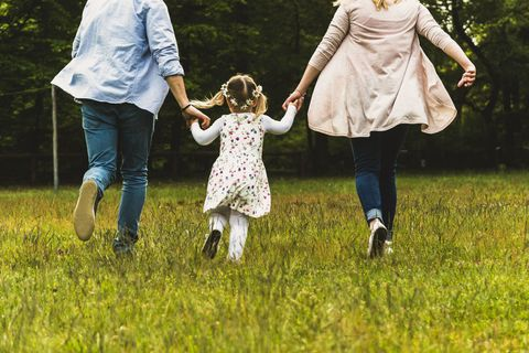 father daughter and mother running in a field