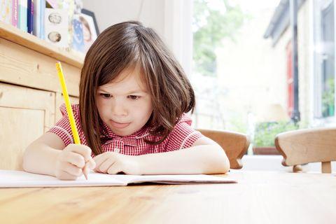 little girl doing homework in the kitchen table