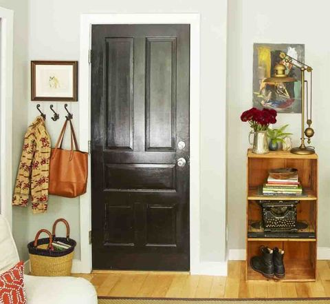<p>Coat hooks and a short bookshelf on opposite sides of the door deliver all the storage of a traditional entry.</p>