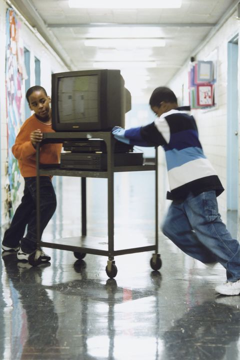 boys pushing TV on a cart