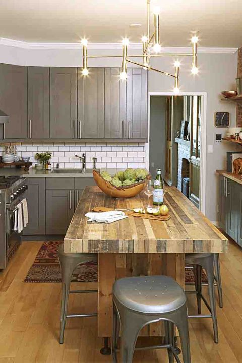 "<p>Prep, serve, and entertain at an island that fits stools underneath, offering seating for a gathering of friends. The homeowners added iron legs to bring this butcher block piece to the right height.</p><p><em>Chandelier, $462, <a href=""http://www.overstock.com/"">overstock.com</a>. Island, <a href=""http://www.westelm.com/"">westelm.com</a>. Cabinetry, <a href=""http://www.ikea.com/"">ikea.com</a>. Blue-striped bowls, $18 each, <a href=""http://www.canvashome.com/"">canvashome.com</a>.</em><br></p>"