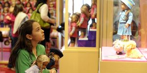 Jazmyn Andre, 10-yesars-old from Parker, looks at an American Girl doll in a glass case, holding two American Girl dolls, one that she already had and another that she just bought at the new American Girl doll store in Park Meadows Mall Friday afternoon.The store had a 'soft opening,' Friday morning, the official opening is Saturday March 27th at 9:00 am. Andre, along with her grandmother, Linda Serrano, and a good friend, (not pictured) had plans on spending the night Friday night, just outside the store for the official opening Saturday morning in which the first 100 customers will get a free 'goodie' bag filled with American Girl doll products. Andy Cross, The Denver Post