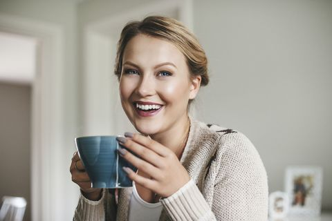 woman smiling and drinking a cup of tea
