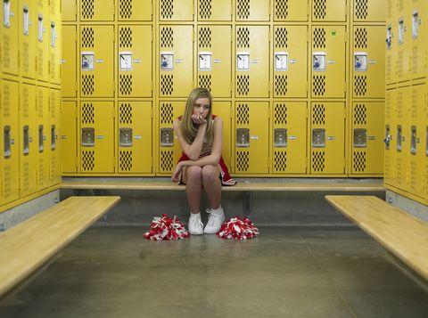 sad cheerleader in locker room