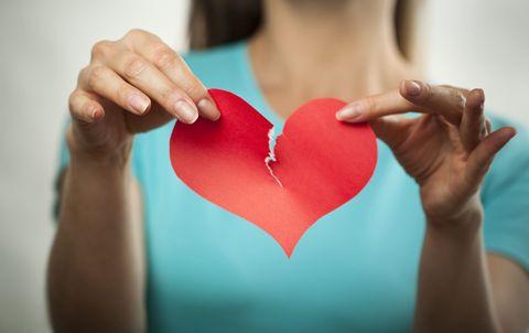 woman tearing paper heart divorce