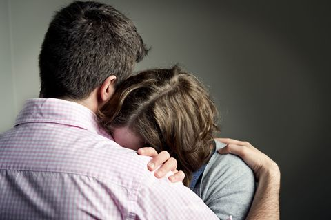 woman crying on husband's shoulder infertility
