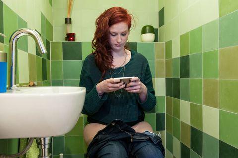 woman on toilet reading phone