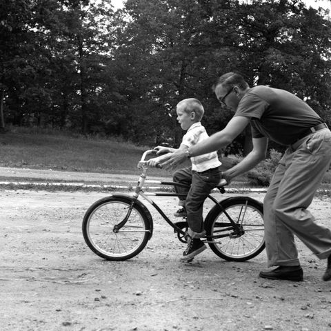 father son riding bicycle no helmet