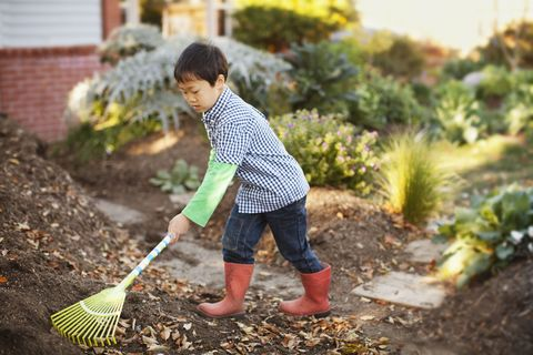 boy raking garden outside single mom chores