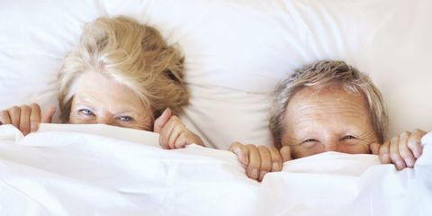 Older Couple under the Sheets in Bed