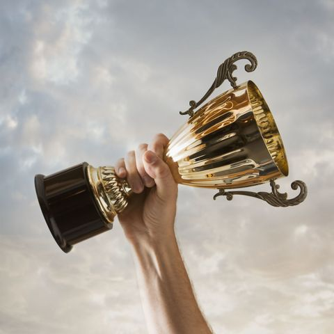 man holding trophy in the air