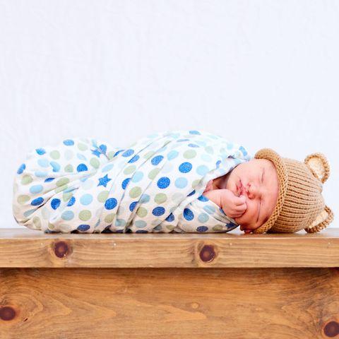 Baby swaddled in polka dot blanket