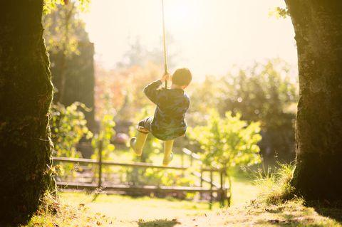 kid playing on swing in backyard
