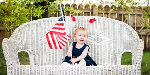 Baby on white wicker bench holding American flag