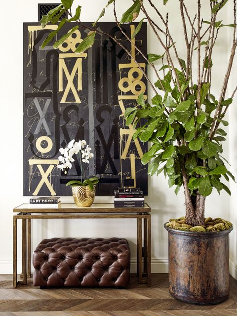 "<p>Tuck away a tufted ottoman beneath a console table in your entry or mudroom. It's easy to pull out for an extra spot to perch when guests come by.</p><p><em><strong>Black-and-gold painting</strong>, Retna. For similar: <strong>Leona Metal Console table in brass, </strong>$599, <a href=""http://www.potterybarn.com/"" target=""_blank"">potterybarn.com</a>. </em><em><strong>Galvanized Barrel planter,</strong> $198, <a href=""http://www.shopterrain.com/"" target=""_blank"">shopterrain.com</a>. <strong>Metallic Belly vase in gold, </strong>$228, <a href=""http://www.jonathanadler.com/"" target=""_blank"">jonathanadler.com</a>.</em></p>"