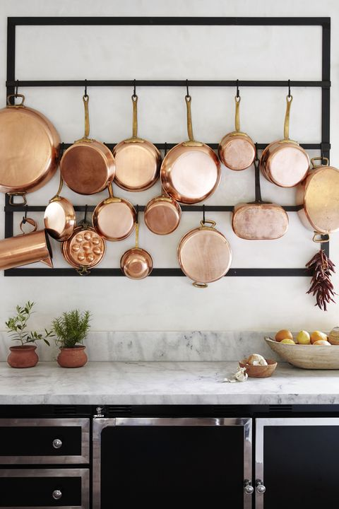 """<p>Arrange them on a wall using a mounted pot rack or a set of sturdy metal hooks. It creates a kitchen-worthy focal point and eliminates cabinet clutter.</p><p><em><strong>Cabinetry, </strong>La Cornue, <a href=""""http://lacornueusa.com/"""" target=""""_blank"""">lacornueusa.com</a>. <strong>Countertops, </strong>Carrara marble.</em><em></em><br></p>"""