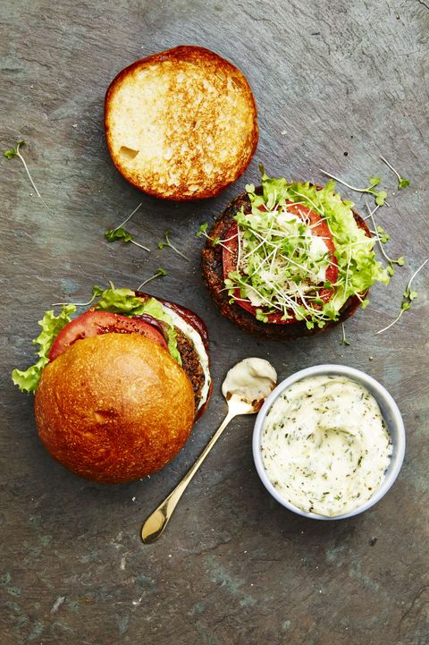 veggie burgers topped with sliced tomatoes, sprouts and creamy sauce