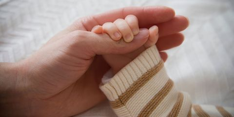 baby and mom holding hands
