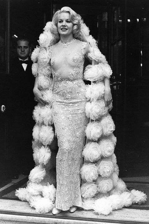 """baker wore this translucent, virtually topless balmain gown to both the us and ukpremiers ofher filmthe carpetbaggers, but it was the red carpet outside london's plaza theaterthat generated the most buzz """"buzz"""" might be putting it too mildly — men actually crashed through apolice wallin an attempt to get a glimpse of baker before she entered the theater"""