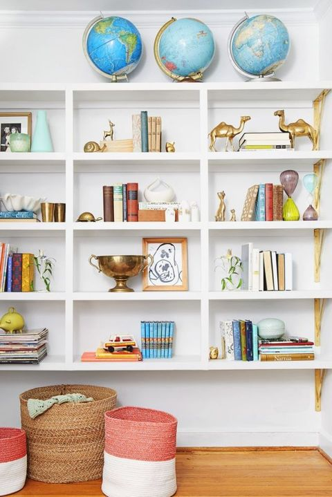 Even ordinary objects, like globes, become standout collectibles when grouped in threes. Toys, books, and brass knickknacks add to the eclectic vibe.