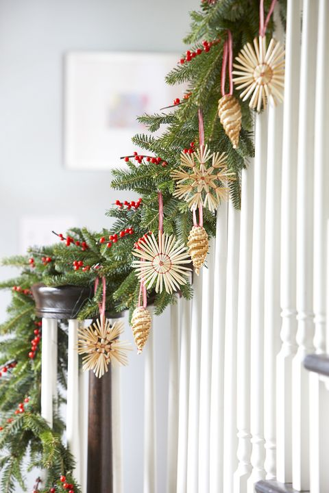 Swedish straw ornaments hung from greenery on staircase. #christmasdecor #swedishchristmas #ornaments #garland