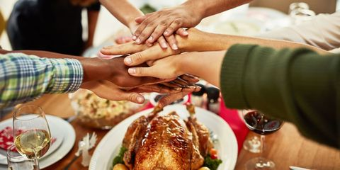 Group holds hands at Thanksgiving table