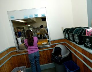 college of the atlantic student in green dining hall, with recycling bins
