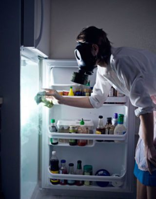 guy in gas mask cleaning refrigerator